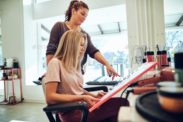 Young woman sitting in a salon chair choosing hair dye - Stock Photo - Images