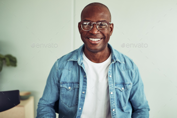 Smiling young African businessman sitting in a modern office - Stock Photo - Images