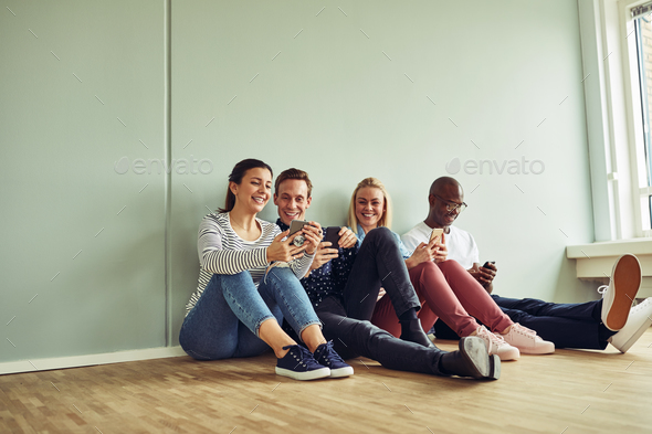 Young coworkers sitting on an office floor during a break - Stock Photo - Images