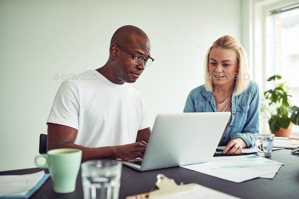 Two businesspeople working online with a laptop together - Stock Photo - Images