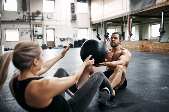 Two fit people exercising with a ball at the gym - Stock Photo - Images
