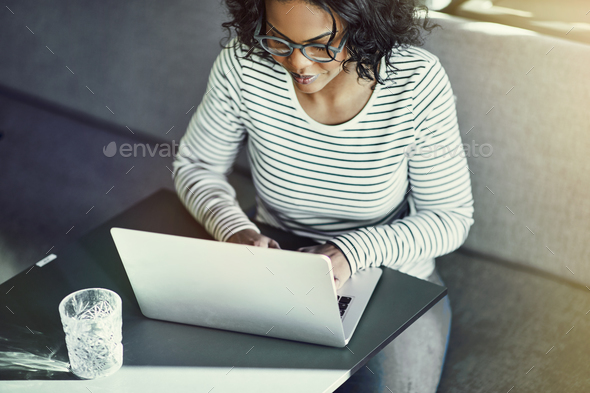 Focused young African woman working online with a laptop - Stock Photo - Images