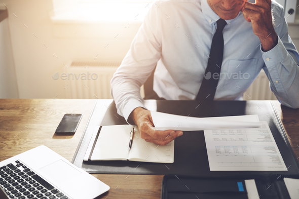 Businessman sitting at an office desk reading through documents - Stock Photo - Images