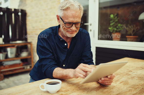 Smiling senior man enjoying a coffee and using a tablet - Stock Photo - Images