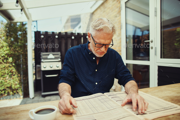 Stern senior man reading a financial newspaper at home - Stock Photo - Images