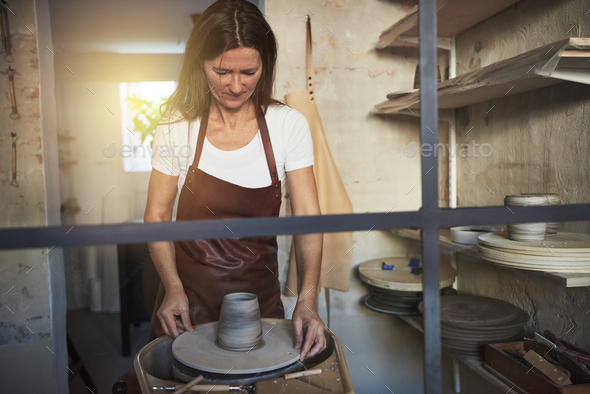 Artisan creatively turning clay on a wheel in her workshop - Stock Photo - Images