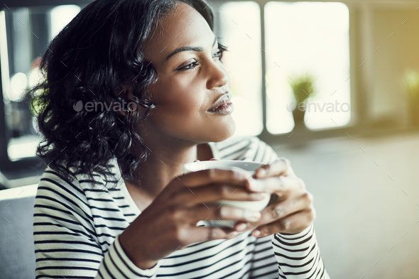Young African woman drinking coffee and looking through a window - Stock Photo - Images