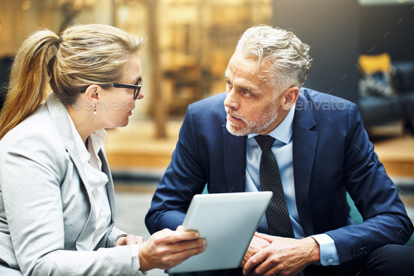 Mature colleagues discussing business together in an office lobby - Stock Photo - Images