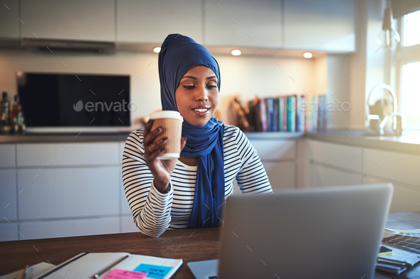 Young Arabic woman drinking coffee and working online at home - Stock Photo - Images