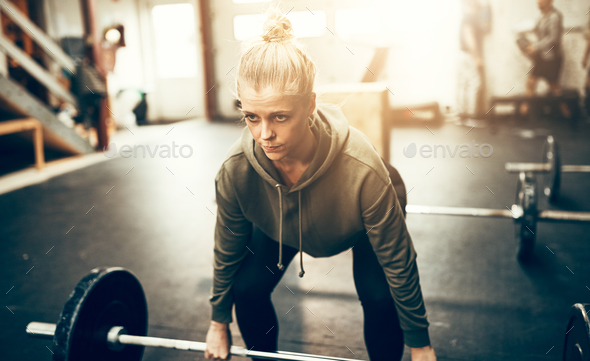 Fit young woman working out with weights in a gym - Stock Photo - Images