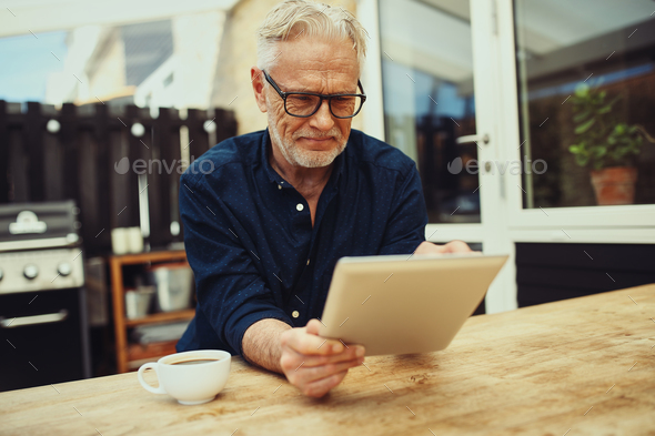 Smiling senior man holding a tablet and drinking coffee outside - Stock Photo - Images