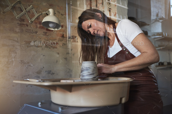 Artisan working on a pottery wheel in her creative studio - Stock Photo - Images