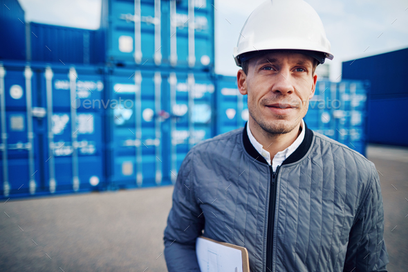 Port manager standing by containers on a commercial freight dock - Stock Photo - Images