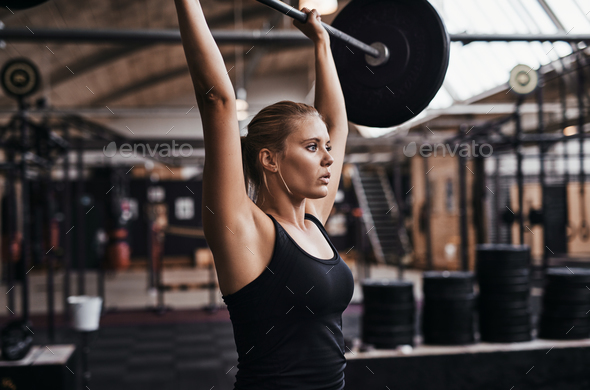 Focused young woman lifting heavy weights in a gym - Stock Photo - Images