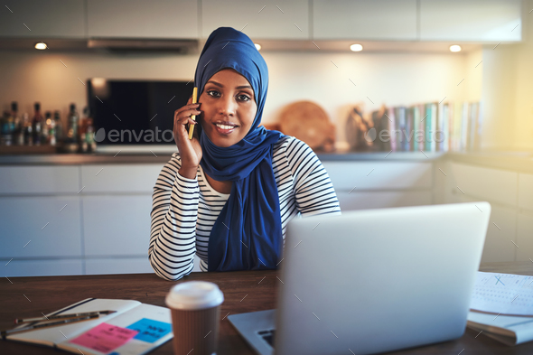 Young Arabic female entrepreneur talking on a cellphone at home - Stock Photo - Images