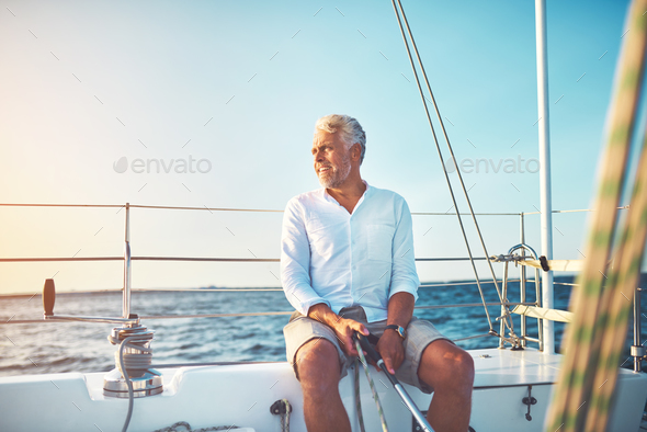 Mature man out for a sail on the open ocean - Stock Photo - Images