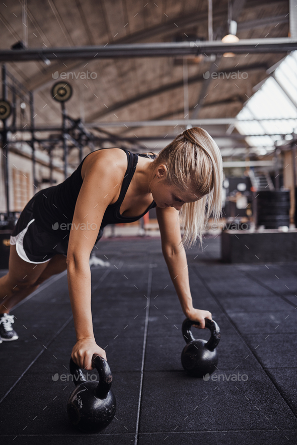 Young woman working out with weights on a gym floor - Stock Photo - Images