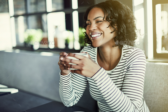 Young African woman laughing while drinking coffee in a cafe - Stock Photo - Images