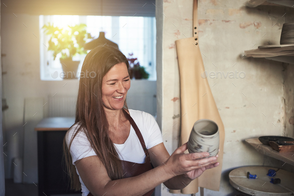 Smiling female artisan inspecting a vase in her creative workshop - Stock Photo - Images