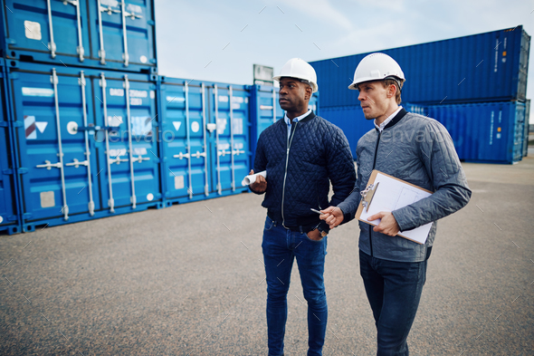 Two engineers discussing logistics in a large shipping yard - Stock Photo - Images