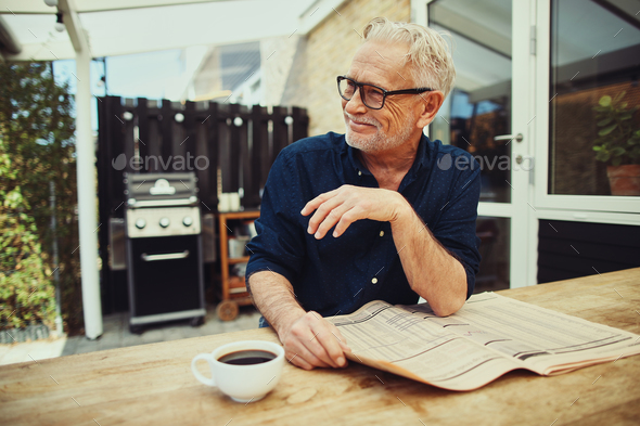 Senior man reading a newspaper outside and drinking coffee - Stock Photo - Images
