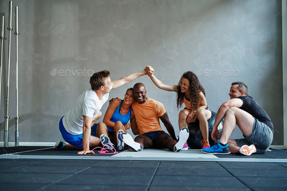 Friends sitting on a gym floor high fiving each other - Stock Photo - Images