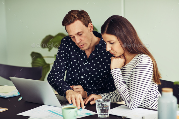 Two office colleagues sitting at a desk discussing paperwork together - Stock Photo - Images