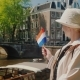 A Woman with the Flag of the Netherlands in Her Hand Admires the Beautiful View of the Canal in - VideoHive Item for Sale