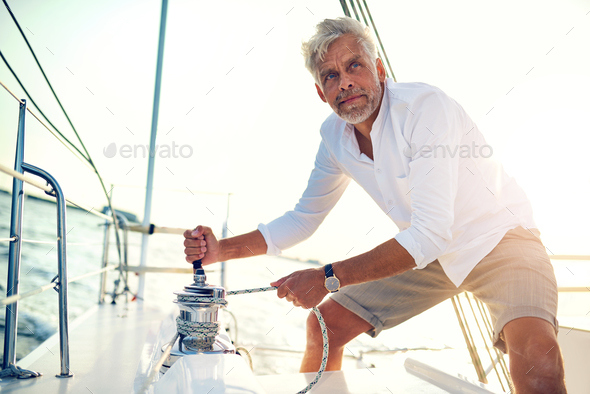 Mature man using a winch while out sailing - Stock Photo - Images
