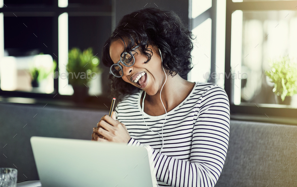 Young African woman laughing while enjoying an online chat - Stock Photo - Images