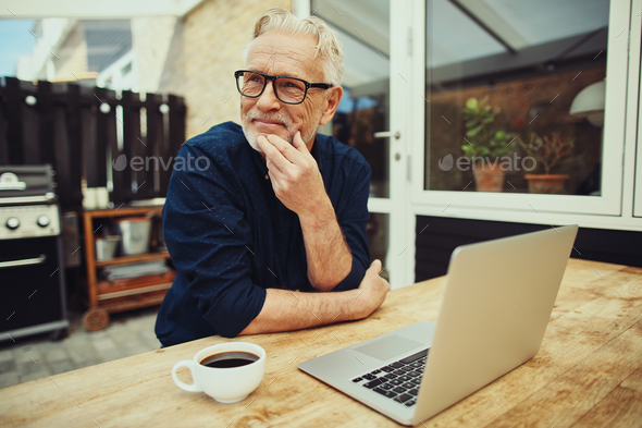 Senior man sitting outside drinking coffee and using a laptop - Stock Photo - Images