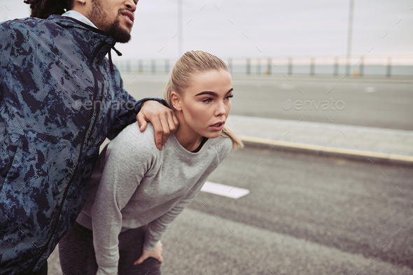 Sporty young couple taking a break together while jogging - Stock Photo - Images