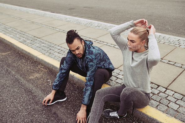 Young couple taking a break on a curb while jogging - Stock Photo - Images