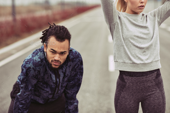 Diverse young couple taking a break from running together - Stock Photo - Images