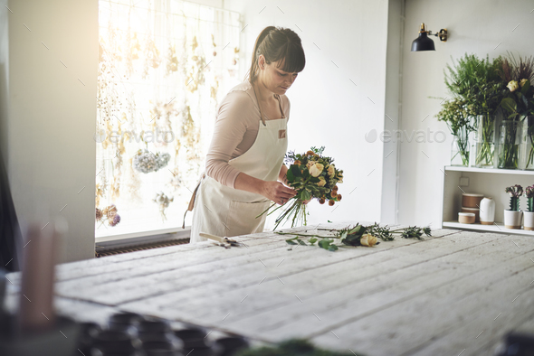 Florist making flower arrangements at a table in her shop - Stock Photo - Images