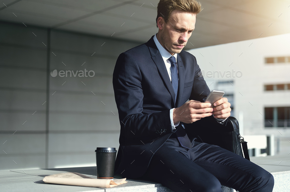 Young stylish businessman while using his phone - Stock Photo - Images