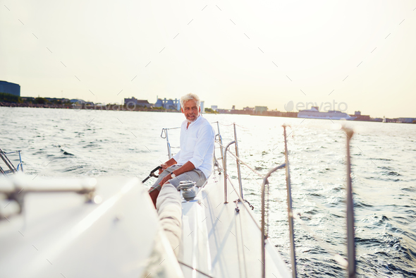 Mature man out sailing his yacht on a sunny afternoon - Stock Photo - Images