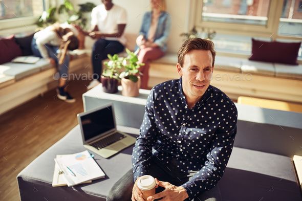 Smiling manager sitting on his desk drinking coffee - Stock Photo - Images