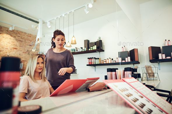 Client and stylist choosing hair dyes during a salon appointment - Stock Photo - Images