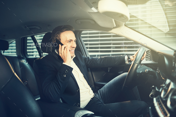 Smiling businessman talking on a phone in his car - Stock Photo - Images