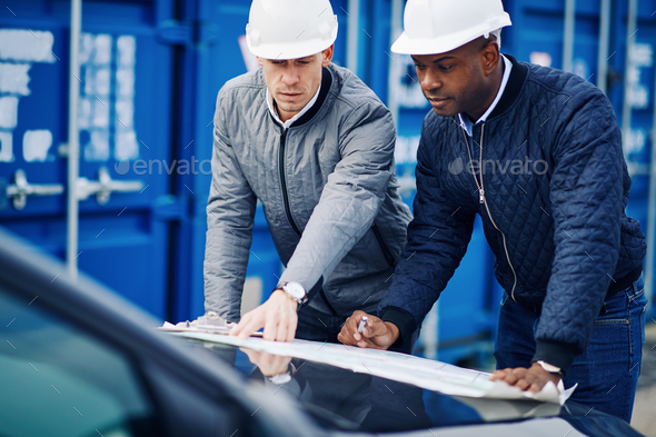 Freight engineers leaning on a truck discussing blueprints - Stock Photo - Images