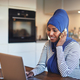Smiling Arabic entrepreneur talking on a phone in her kitchen - PhotoDune Item for Sale