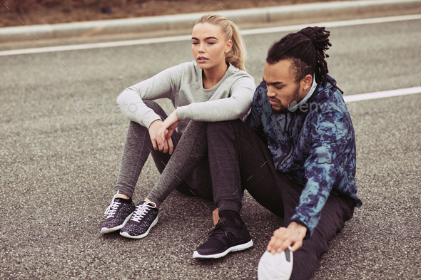 Young couple resting while out for a run together - Stock Photo - Images