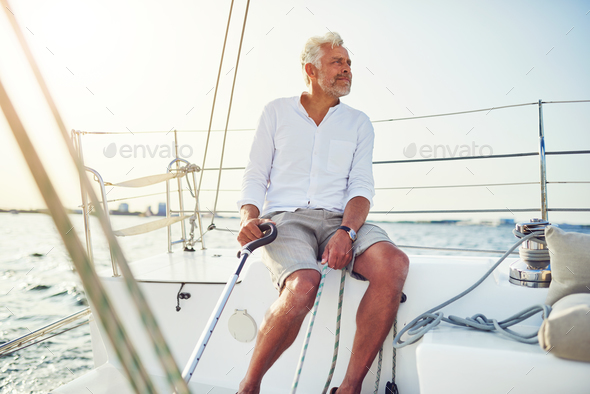 Mature man out for a sail on the ocean - Stock Photo - Images
