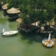 Summer Bungalows with Thatched Roof and Boat in Green Lake in Water Villa Resort Drone View. People - VideoHive Item for Sale