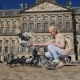 A Young Woman Is Feeding Pigeons in the Center of Amsterdam in Dam Square. Tourism in Europe and the - VideoHive Item for Sale
