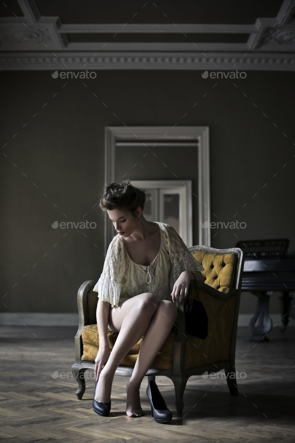 Woman sitting on an armchair - Stock Photo - Images