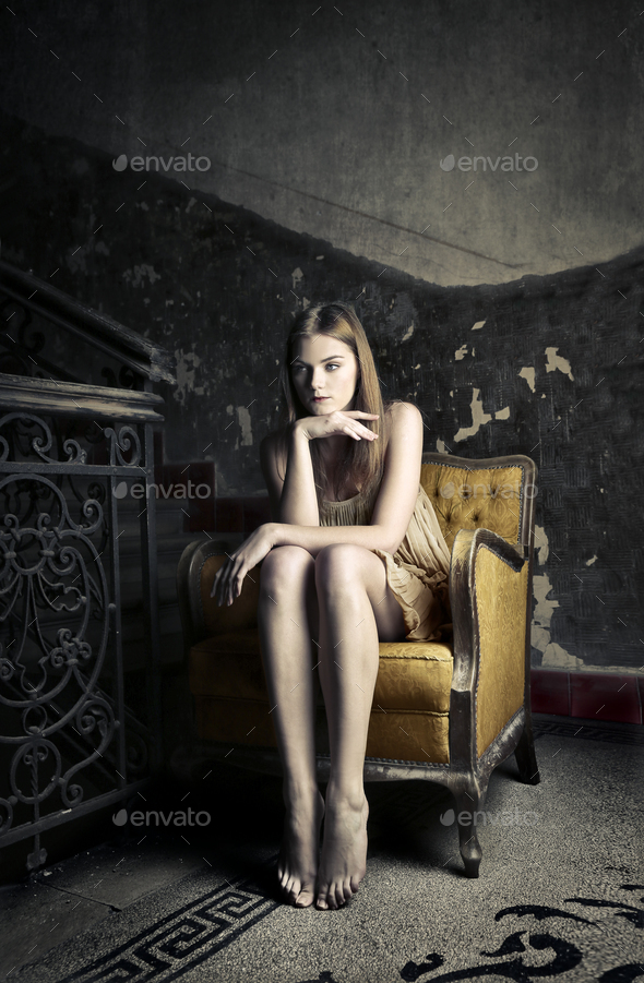 Girl sitting on an armchair - Stock Photo - Images
