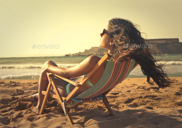 Girl sitting on a deckchair - Stock Photo - Images
