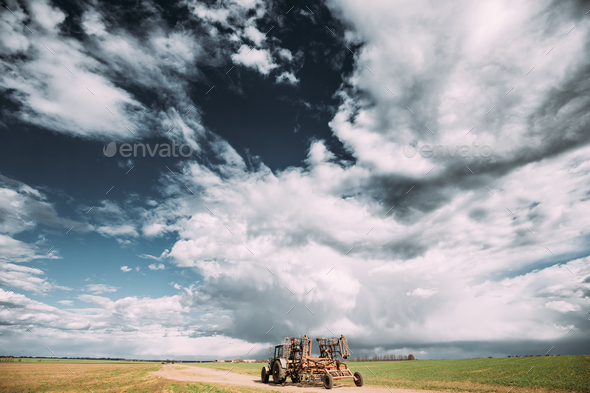 Tractor With Attached Harrow In Sunny Spring Day. Countryside Ru - Stock Photo - Images
